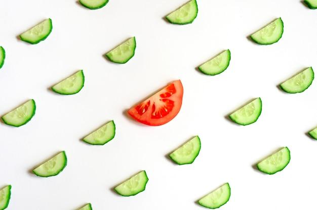 サラダ用の新鮮な生野菜きゅうりのスライスされた半円と白い背景に分離された中央のトマトのスライスの繰り返しパターンフラットレイ、上面図