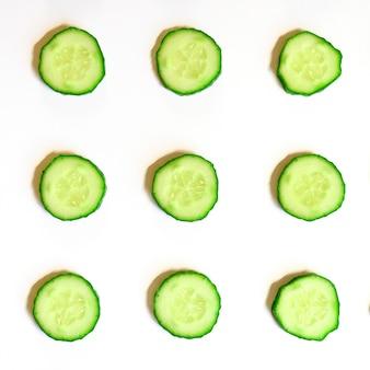 Повторяющийся узор из нарезанных полукругов свежих сырых овощных огурцов для салата, изолированные на белом фоне плоской планировки, вид сверху. квадрат