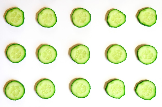 Repeating pattern of sliced semicircles of fresh raw vegetable cucumbers for salad isolated on a white background flat lay, top view
