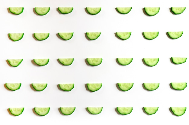 Repeating pattern of sliced semicircles of fresh raw vegetable cucumbers for salad isolated