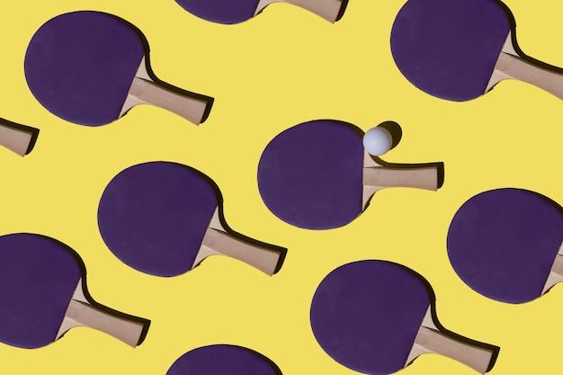 노란색 배경에 반복되는 탁구 라켓과 공