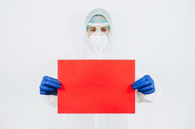 防護服、reperitor、手袋の医師は、白い壁に赤い紙のシートを保持しています。テキストのための場所。医者はコロナウイルスと闘っています。 covid-19ウイルス。医師は家にいるように勧めた