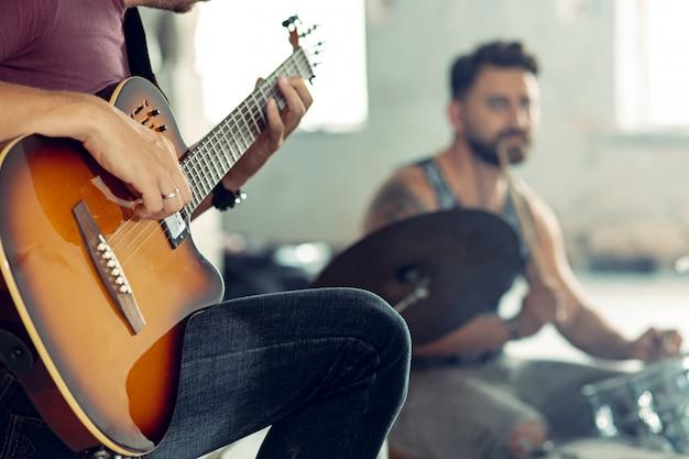 ロックミュージックバンドの繰り返し。エレクトリックギタープレーヤーとドラムセットの背後にあるドラマー。