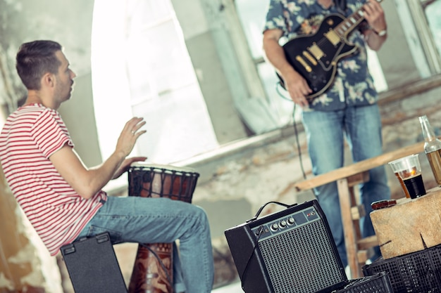 Repetition of rock music band. electric guitar player and drummer behind the drum set.
