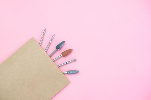 Сменные насадки для маникюрного аппарата в пакете для рукоделия после стерилизации. на розовом фоне с копией пространства