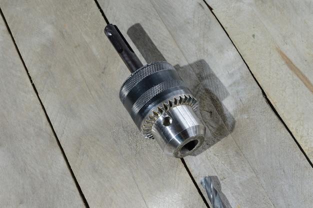 交換可能なドリルチャックと古いドリルビットは、木の板の背景にあります。閉じる。