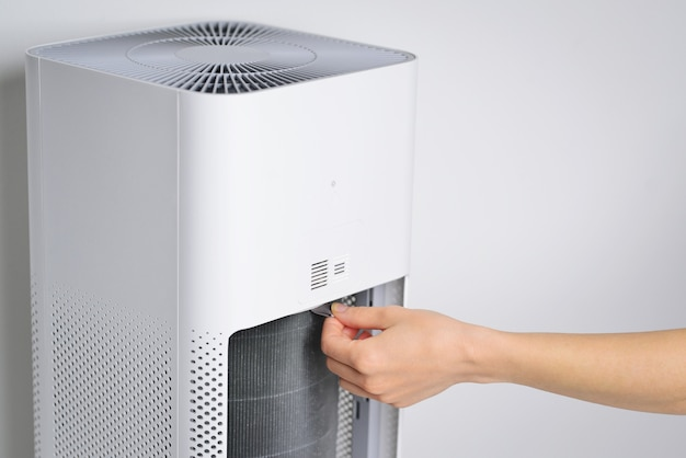 Replaced a new filter into the air purifier machine preventing allergies pm 25 dirty air filter need to maintenance hand a man open the lid of the air purifier check and change filter in side air