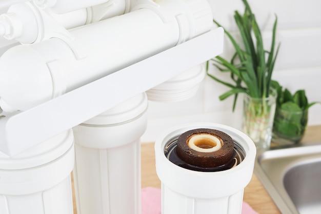 가정용 주방에서 더러운 정수 필터 카트리지를 교체하십시오. 정화 삼투 시스템을 수정합니다.