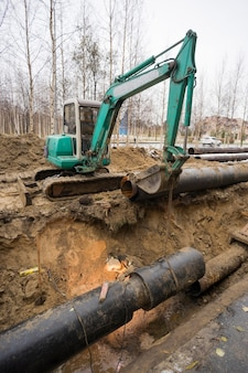 Replacement of old pipes with new ones ,the welder works in the excavated pit.