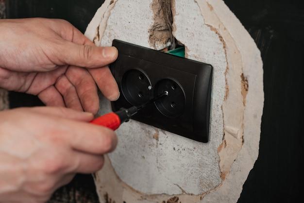 新しいコンセントの交換と取り付け。ドライバーの男性の電気技師の手