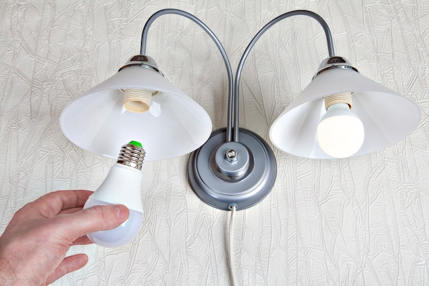 Replacing electric light bulbs in household wall lamp, led light bulb in human hand, close-up.