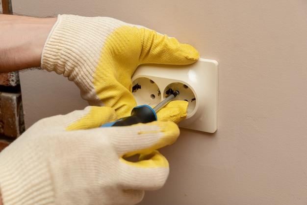보호 고무 장갑을 끼고 손으로 전기 소켓, 콘센트 교체, 설치