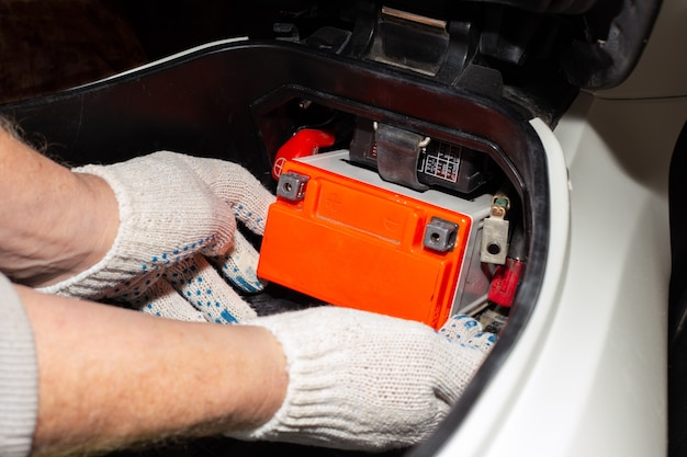 Replacing the motorcycle battery an auto mechanic in a car service takes the battery out of the