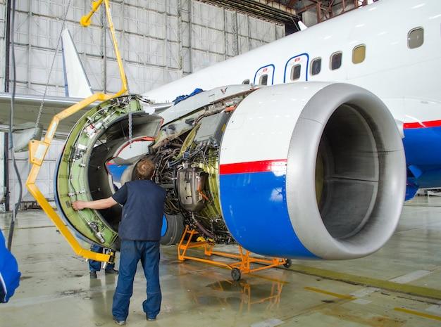 비행기에서 엔진을 교체하면 일하는 사람들이 탭합니다. 항공기의 개념 유지 보수.