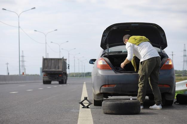 道路上の車のホイールを交換します。傍観者としてタイヤの仕事をしている男性。