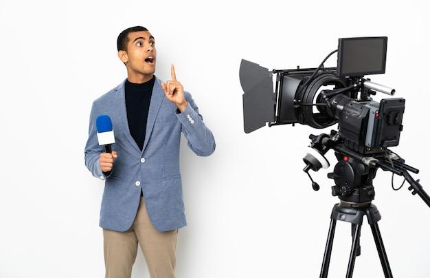 マイクを持って、指を上に向けるアイデアを考えている孤立した白のニュースを報告するレポーターアフリカ系アメリカ人の男