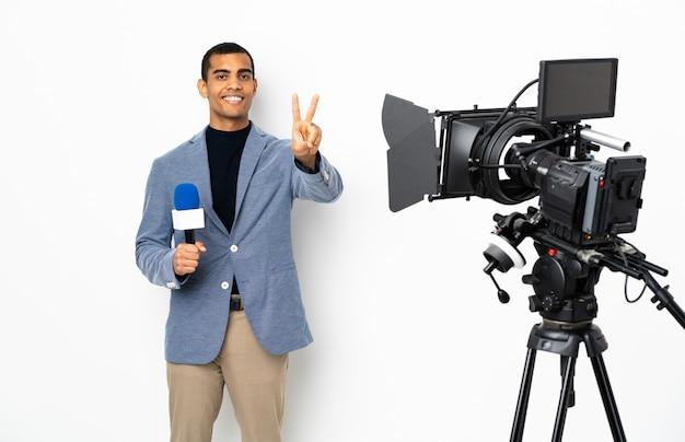 マイクを押しながら笑みを浮かべて勝利のサインを示す分離の白い壁にニュースを報告するアフリカ系アメリカ人記者