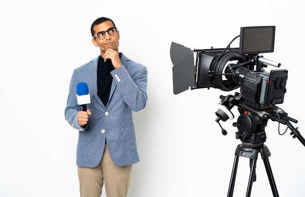 Репортер афроамериканец мужчина держит микрофон и сообщая новости на белом фоне, думая, идея глядя