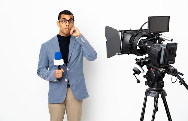 Репортер афроамериканец мужчина держит микрофон и сообщая новости на белом фоне, думая, идея