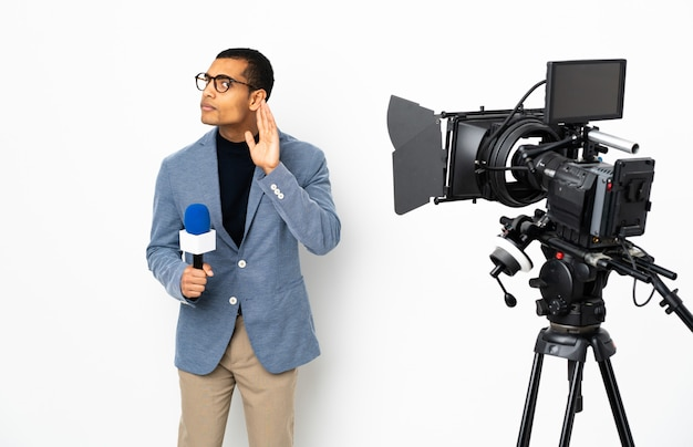 Reporter african american man holding a microphone and reporting news over isolated white wall listening to something by putting hand on the ear