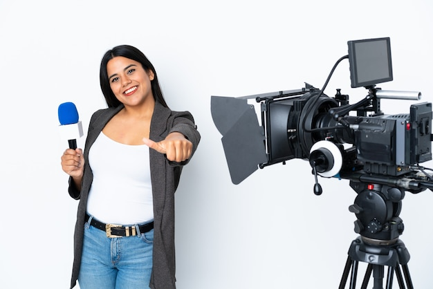 Reporter colombian woman holding a microphone and reporting news on white giving a thumbs up gesture