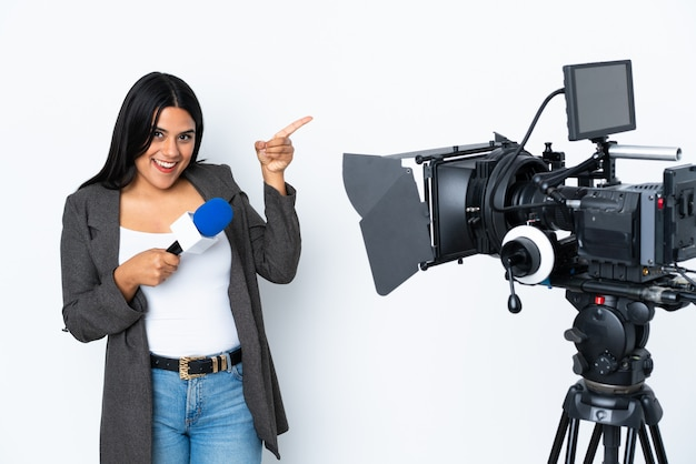 Reporter colombian woman holding a microphone and reporting news on white pointing finger to the side and presenting a product