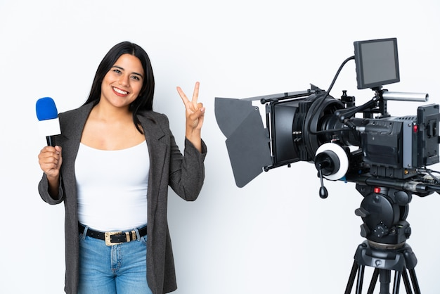 Reporter colombian woman holding a microphone and reporting news on white showing victory sign with both hands