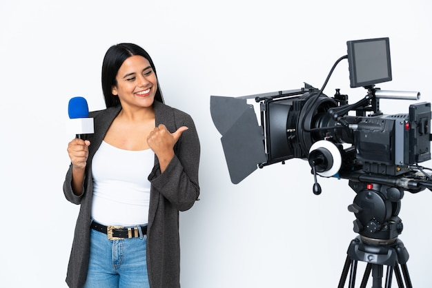Reporter colombian woman holding a microphone and reporting news on white wall pointing to the side to present a product