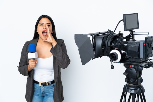 Reporter colombian woman holding a microphone and reporting news on white wall shouting with mouth wide open