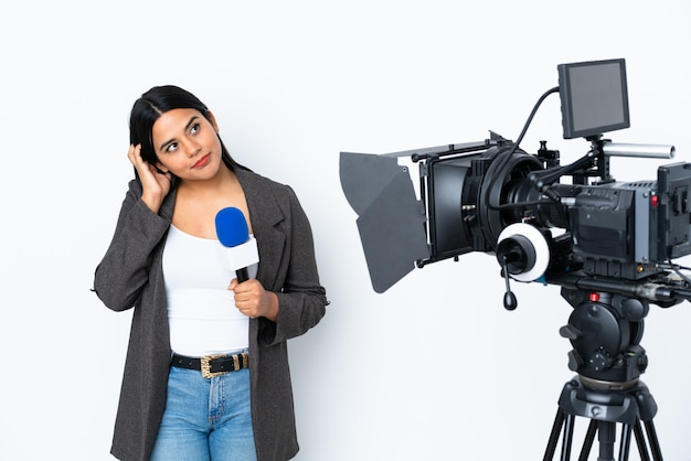 Reporter colombian woman holding a microphone and reporting news on white wall thinking an idea