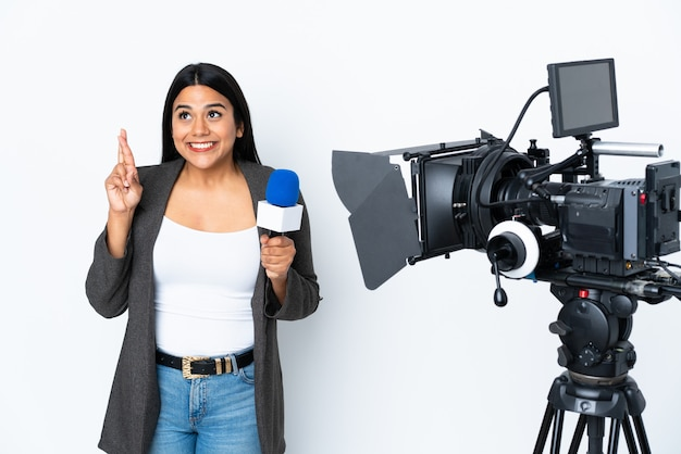 Reporter colombian woman holding a microphone and reporting news on white with fingers crossing