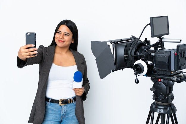 Reporter colombian woman holding a microphone and reporting news on white