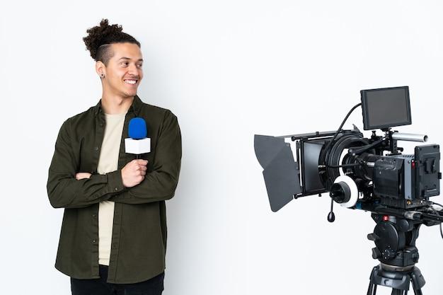 Репортер мужчина держит микрофон и сообщает новости смеясь