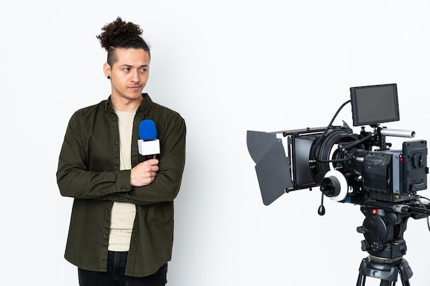 マイクを持って、アイデアを考えてニュースを報告する記者男
