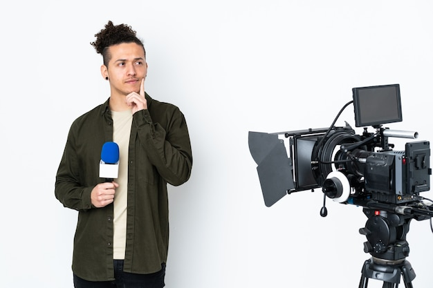 マイクを持って、アイデアを考えてニュースを報告する記者の男