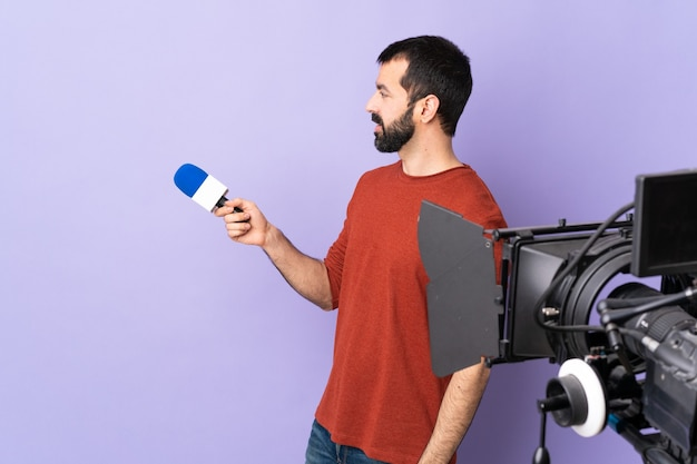 Reporter man holding a microphone and reporting news on isolated purple