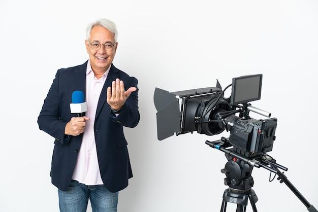 Репортер бразильский мужчина средних лет, держащий микрофон и репортаж о новостях, изолированы, приглашая протянуть руку. счастлив что ты пришел