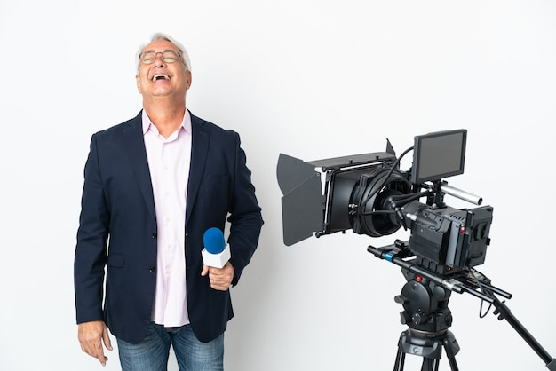 Репортер среднего возраста бразильский мужчина держит микрофон и сообщает новости, изолированные от смеха