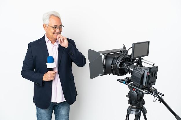 Репортер среднего возраста бразильский мужчина держит микрофон и сообщает новости изолированно смотрит в сторону и улыбается