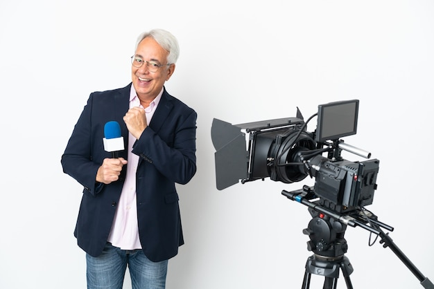 기자 중년 브라질 남자는 마이크를 들고 승리를 축하하는 흰색 배경에 고립 된 뉴스를보고
