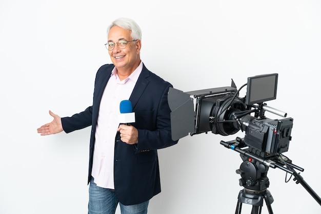 Репортер среднего возраста бразильский мужчина держит микрофон и сообщает новости на белом фоне, протягивая руки в сторону, чтобы пригласить приехать