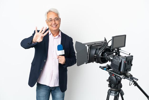 Репортер среднего возраста бразильский мужчина держит микрофон и сообщает новости, изолированные на белом фоне, счастлив и считает четыре пальцами