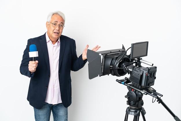 Репортер среднего возраста бразильский мужчина держит микрофон и сообщает новости на белом фоне, сомневаясь, поднимая руки