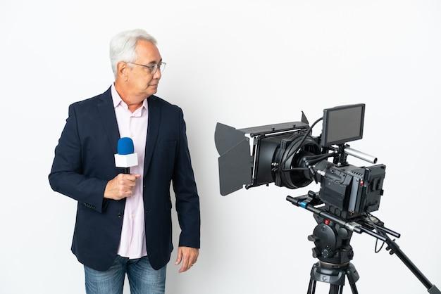 Репортер среднего возраста бразильский мужчина держит микрофон и сообщает новости, изолированные на белом фоне, глядя в сторону