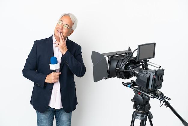 기자 중년 브라질 남자가 마이크를 잡고 웃고있는 동안 올려 흰색 배경에 고립 된 뉴스를보고