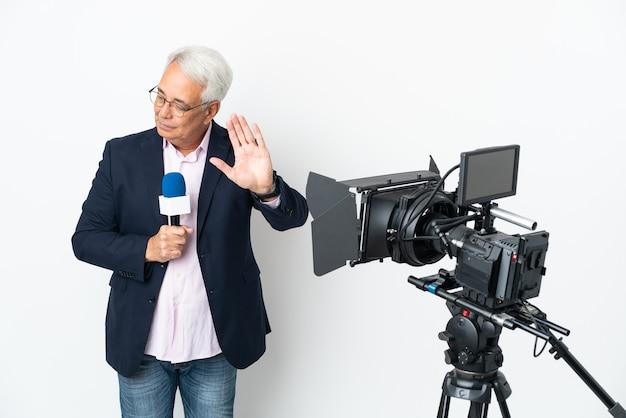 Репортер среднего возраста бразильский мужчина держит микрофон и сообщает новости, изолированные на белом фоне, делая жест стоп и разочарованный