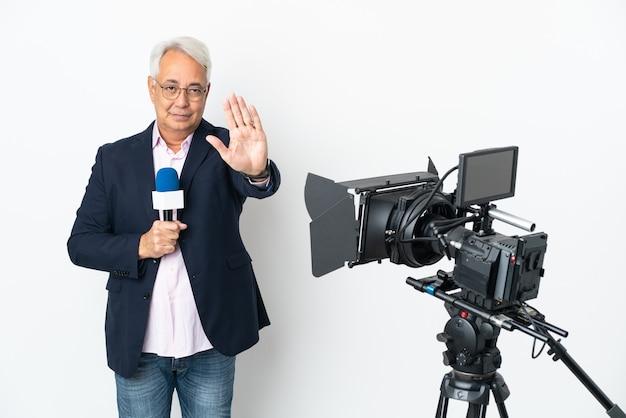 Репортер среднего возраста бразильский мужчина держит микрофон и сообщает новости, изолированные на белом фоне, делая стоп-жест