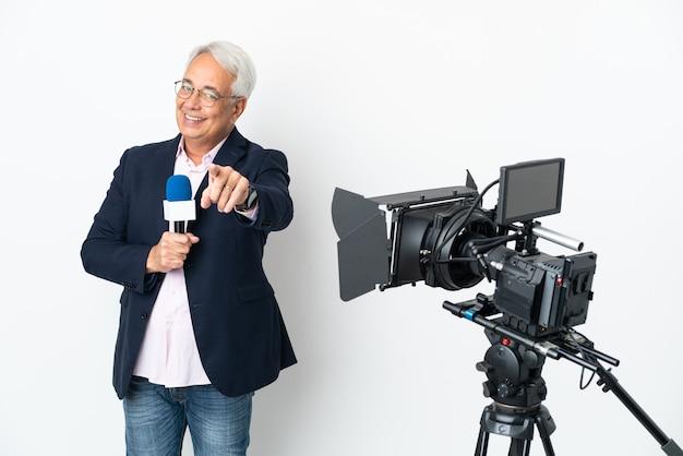 기자 중년 브라질 남자는 마이크를 들고 행복한 표정으로 앞을 가리키는 흰색 배경에 고립 된 뉴스를보고합니다.