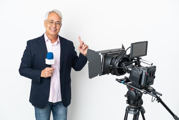 Репортер среднего возраста бразильский мужчина держит микрофон и сообщает новости на белом фоне, указывая на отличную идею