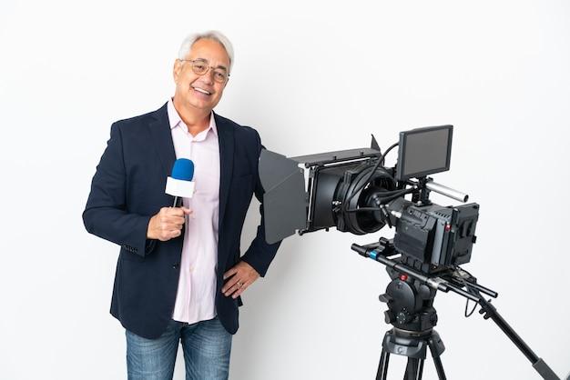 Репортер среднего возраста бразильский мужчина держит микрофон и сообщает новости, изолированные на белом фоне, позирует с руками на бедрах и улыбается